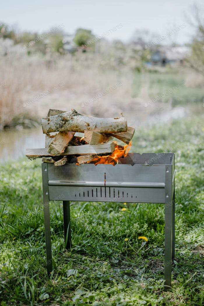 Metal portable barbecue with burning firewood and red flames. Picnic outdoor BBQ Barbecue. Bonfire