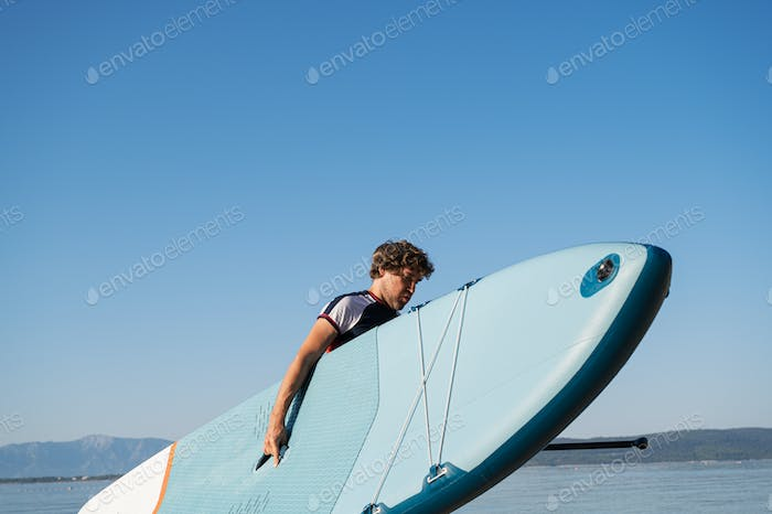 Young man carrying blue sup board out of the water