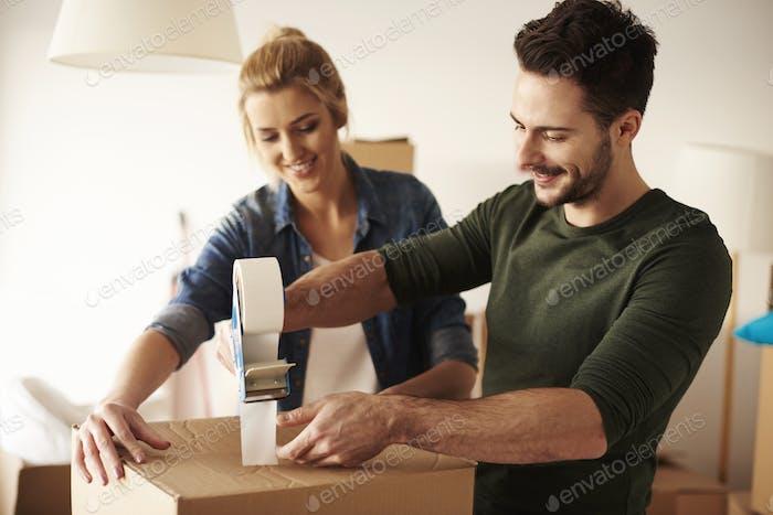 Man taping cardboard box to move