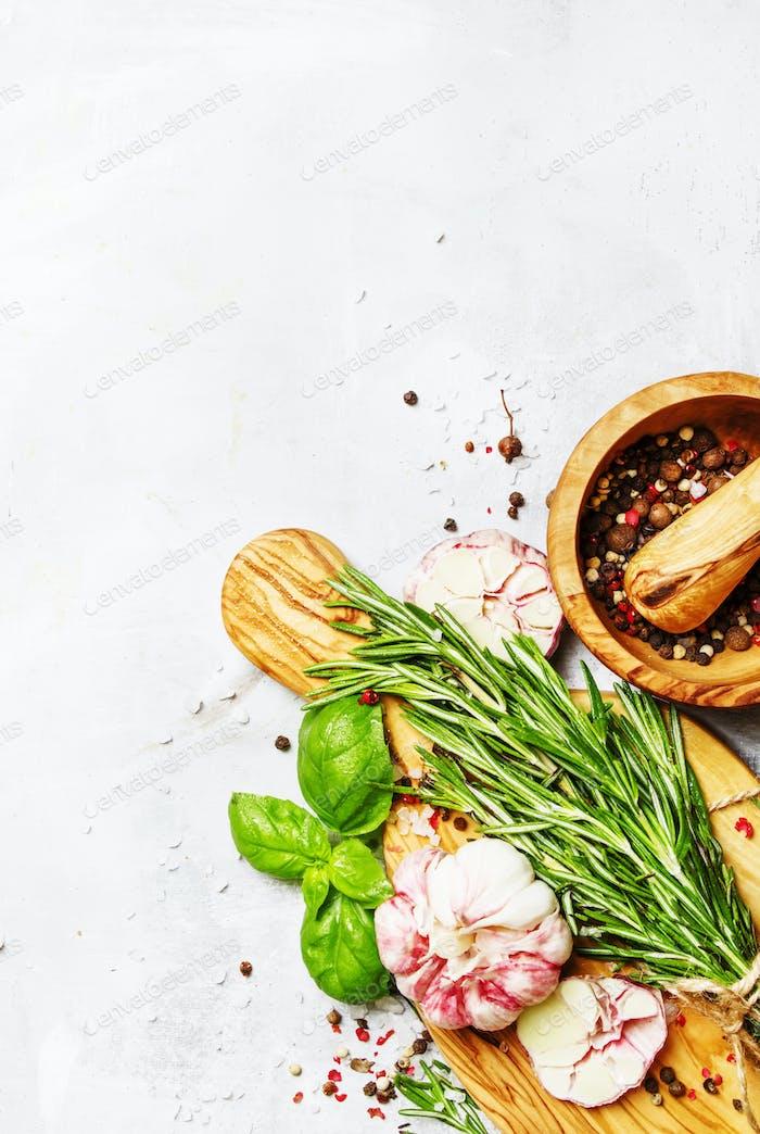 Food background, fresh rosemary, green basil, garlic, pepper
