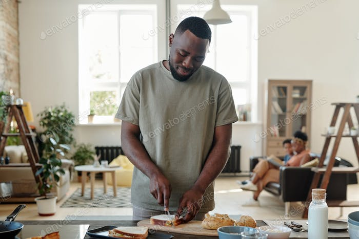 Young bearded man of African ethnicity preparing sandwiches for breakfast