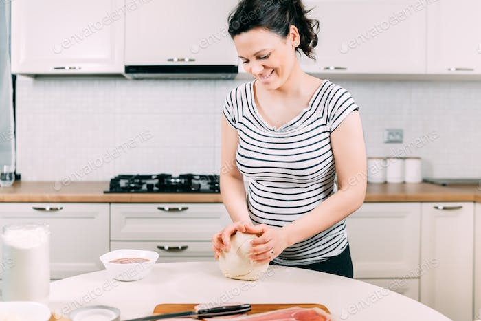 professional pregnant cook in kitchen prepares the dough with flour to make bio pizza.