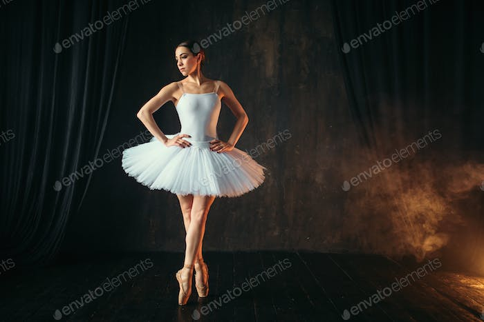 Ballerina in white dress and pointe shoes dancing