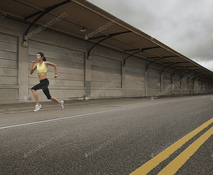 A woman running along an urban road, arms working and legs striding out.