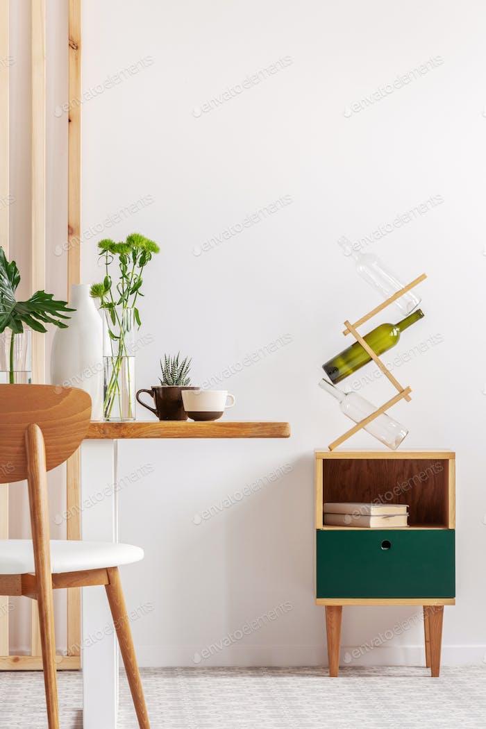 Grüne Blätter in Vasen auf langen Holztisch im trendigen weißen Esszimmer