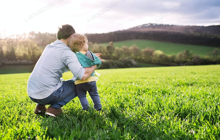 A father with his toddler son outside in spring nature. Copy space.