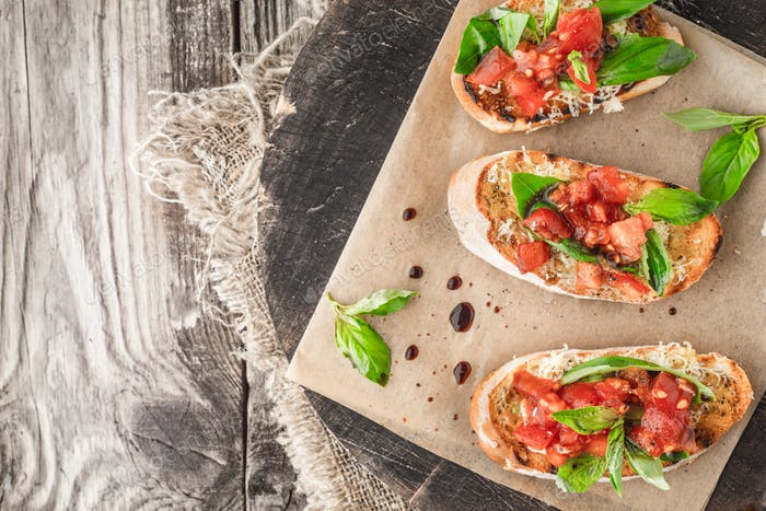 Bruschetta with tomatoes and basil on the wooden board top view