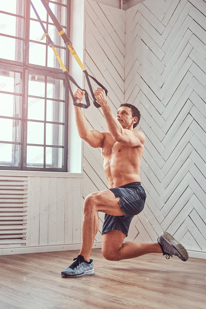 Shirtless muscular male doing exercise with TRX.