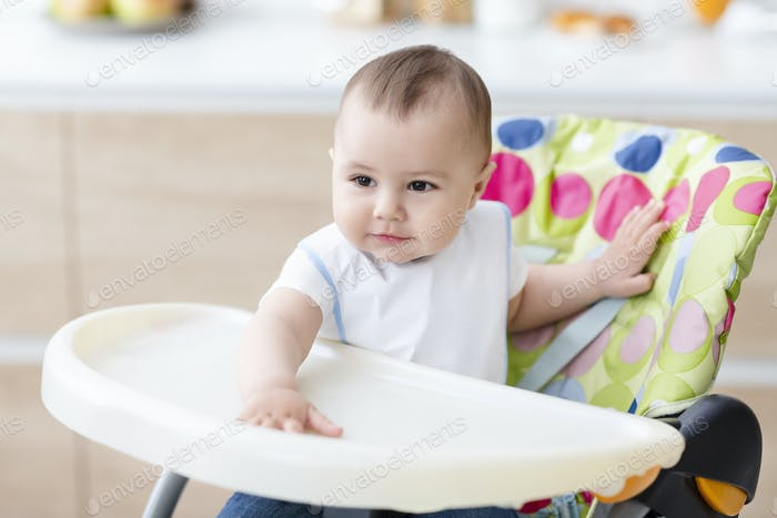 Cute baby sitting in high chair in kitchen