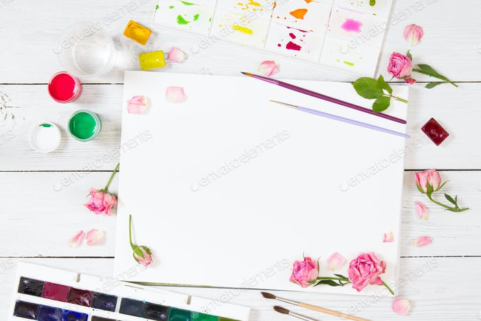 Sketchbooks, brushes, watercolor paints, palette and pink roses