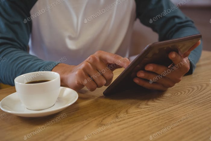 Mid section of man with coffee using tablet in cafe