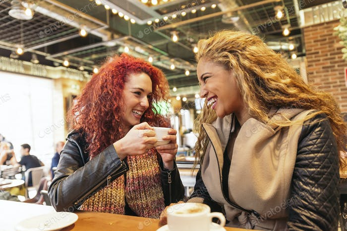 Happy attractive friends at the cafe enjoying in a cafe