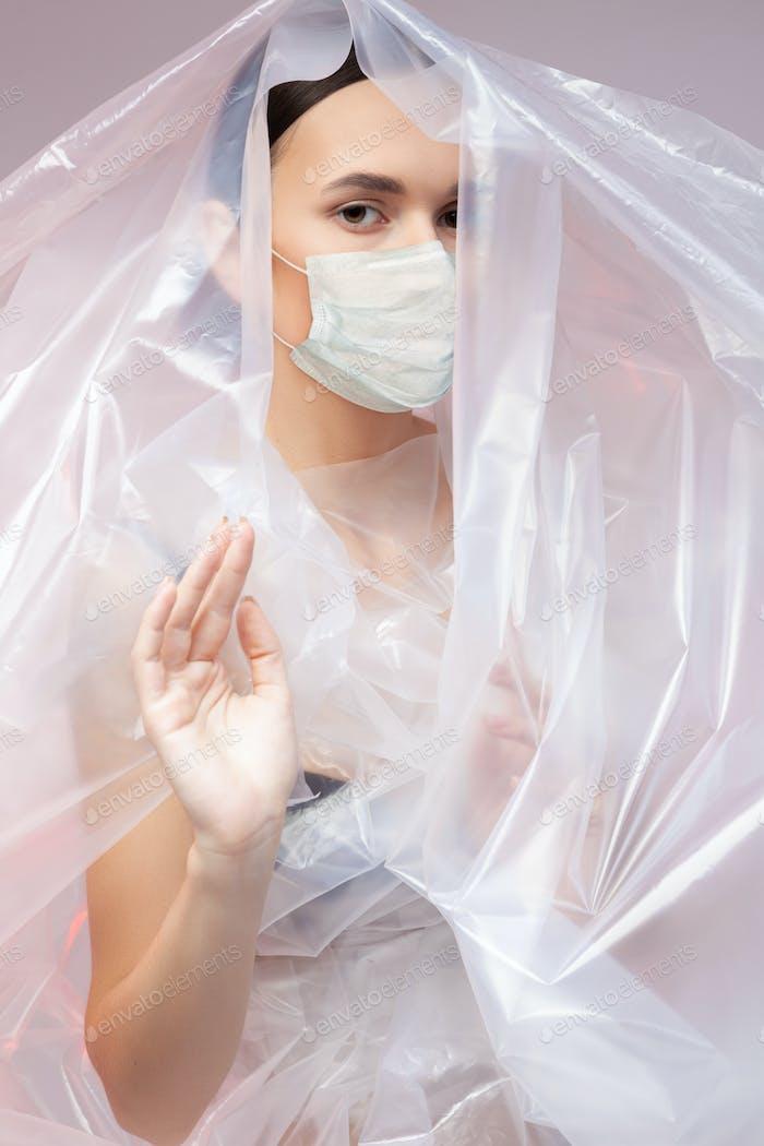 Fashion woman in polyethylene wearing protective mask