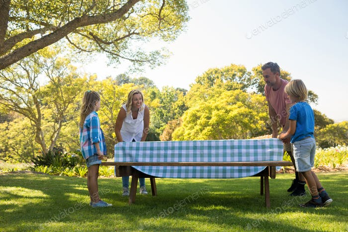 Family spreading the tablecloth on picnic table