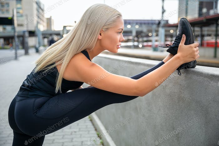 Determined Young Woman Stretching Leg On Railing In City