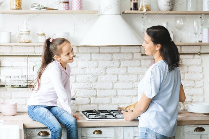 Smiling girl and her mom preparing dinner together