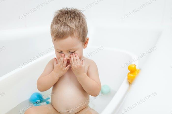 Adorable child in the bathroom having a bath