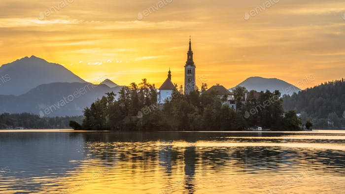 Famous Island in Lake bled with church under orange morning sky
