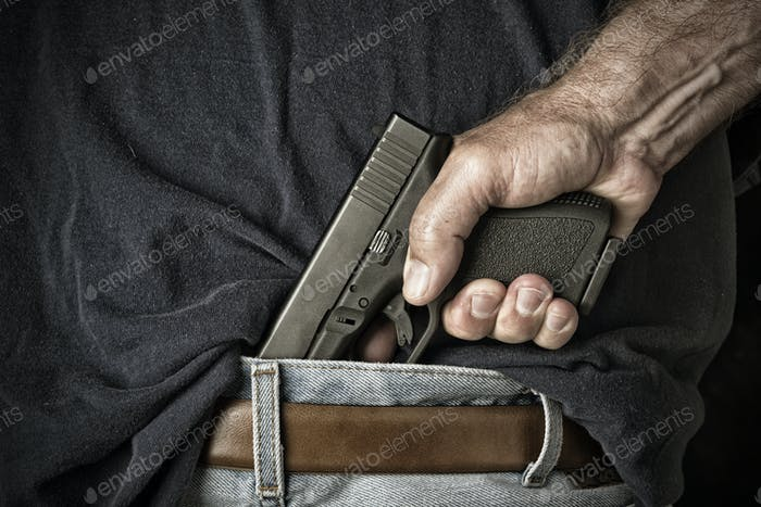 Man pulling gun from waistband