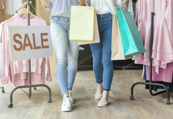 Legs of two girls holding shopping bags near sale board