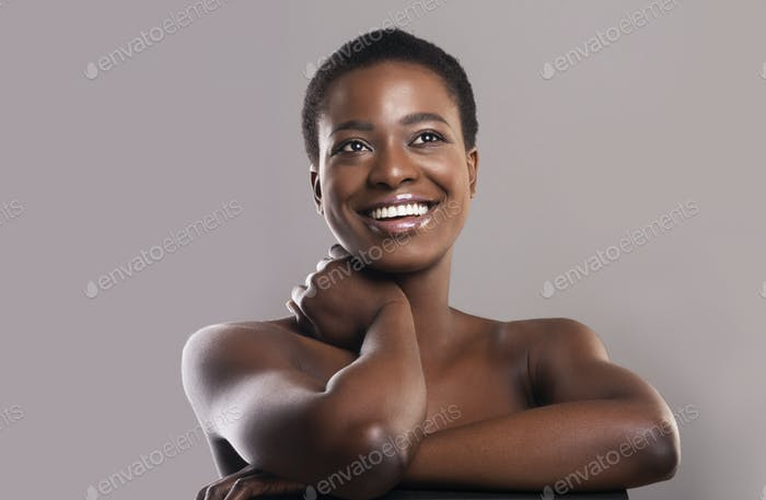 Closeup portrait of dreamy nude black woman over gray background