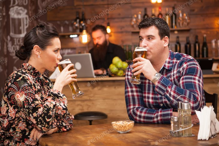 Romantic Couple drinking beer in in a hipster pub and making a toast