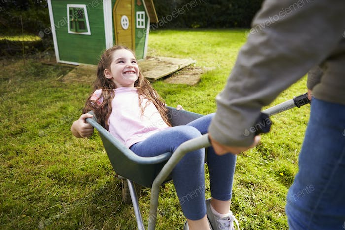 Brother Pushing Sister In Garden Wheelbarrow