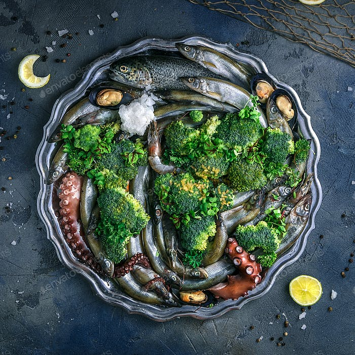 Variety of fresh seafood on a plate with green vegetables