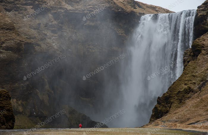 Tourists enjoying the Skogafoss waterfall and river in Iceland