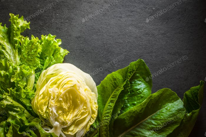 Green salad, iceberg lettuce and spinach left on the table