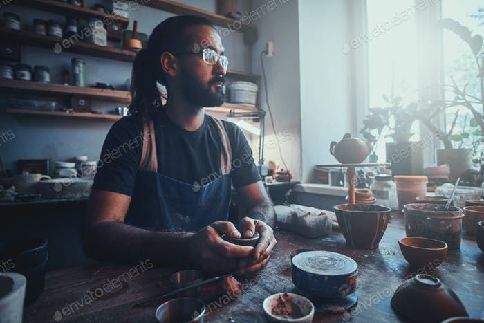 Pensive artist at his own pottery studio is workig for new project.