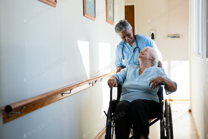 Nurse talking while pushing patient sitting in wheelchair