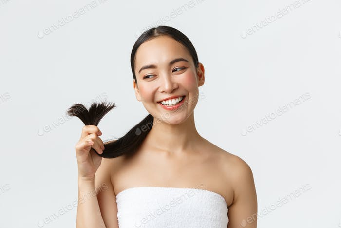 Beauty, hair loss products, shampoo and hair care concept. Gorgeous happy asian woman in bath towel