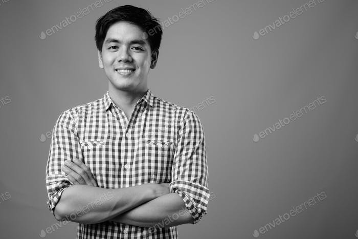 Portrait of young handsome Filipino hipster man