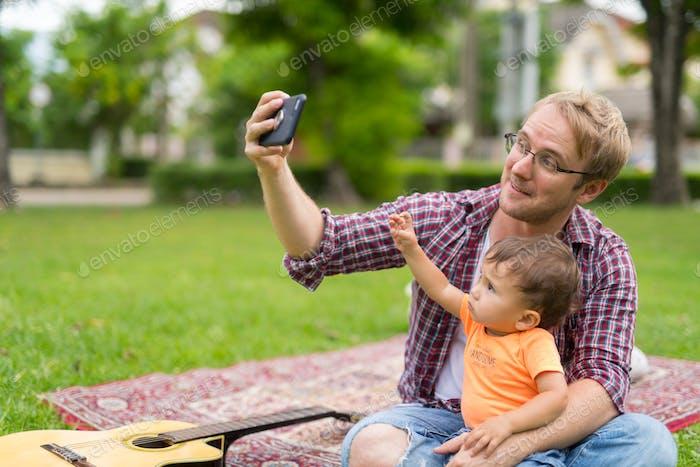 Happy Vater und Baby Sohn nehmen selfie zusammen im freien