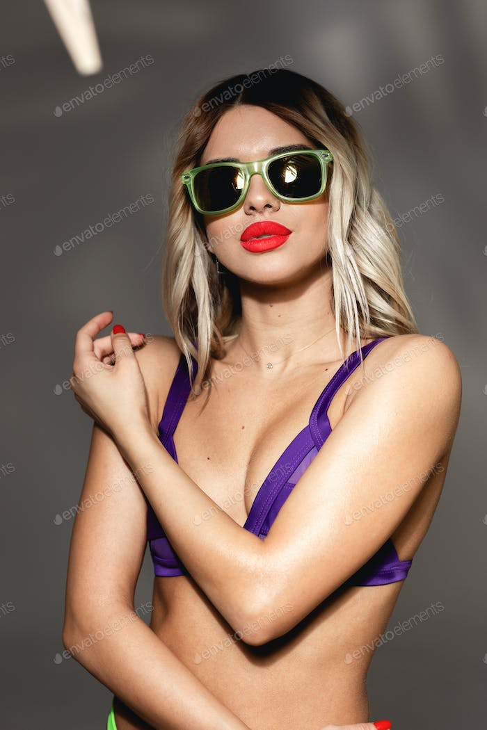 Blond girl with red lipstick and sunglasses on her face dressed in sexy acid purple swimsuit is