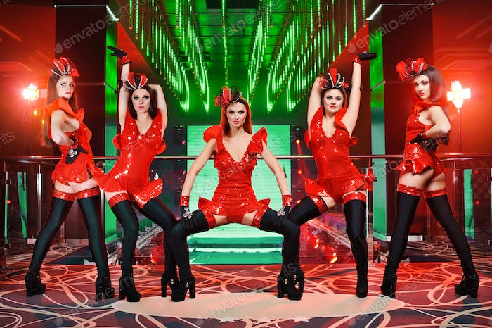 Group of sexy female dancers in red matching outfits performing