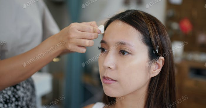 Asian woman having make up by artist in the studio