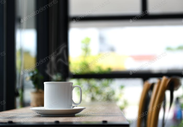 Coffee with smoke on wooden table.
