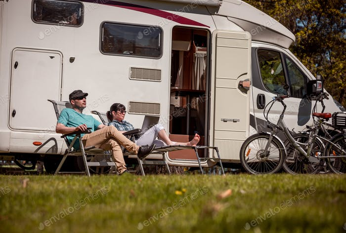 Woman with a man resting near motorhomes in nature. Family vacat