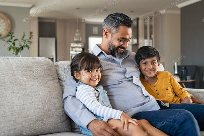 Father sitting with kids on couch