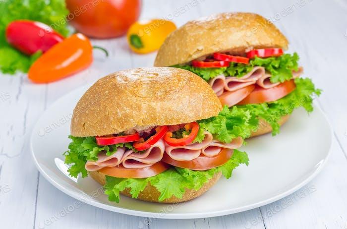 Gesunde Schinken-Sandwiches auf dem Teller mit Gemüse auf dem Hintergrund