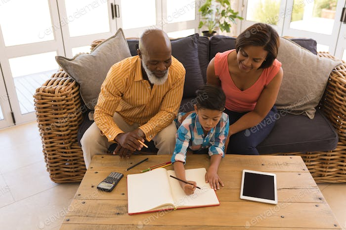 Helpful grandfather and grandmother helping their grandson with homework in living room
