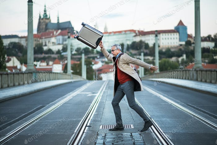 A happy mature businessman with suitcase crossing a road in Prague city.