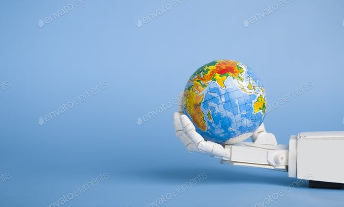Earth globe in robotic hand, blue panorama background