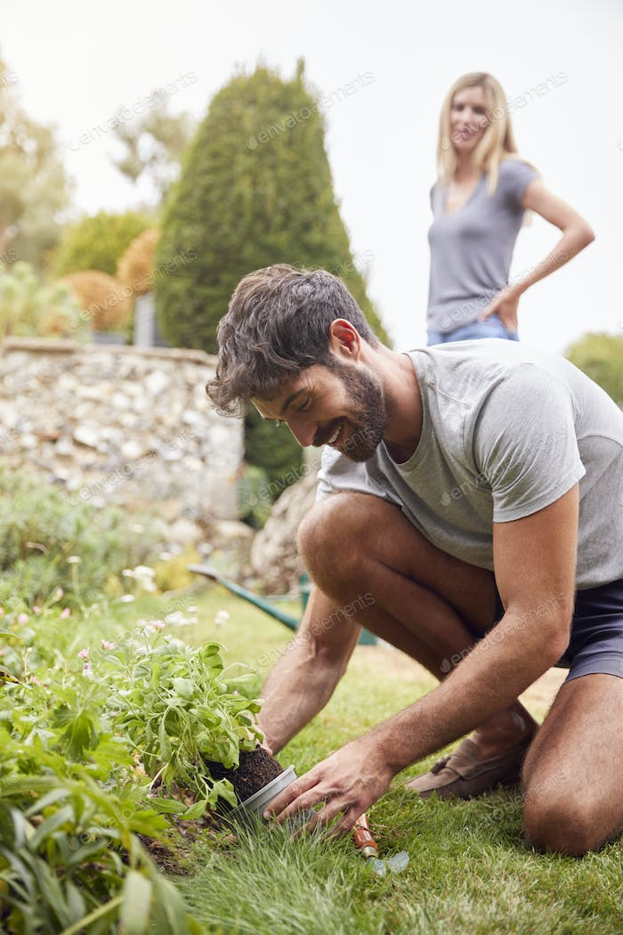 Couple Working Outdoors In Garden At Home Digging And Planting