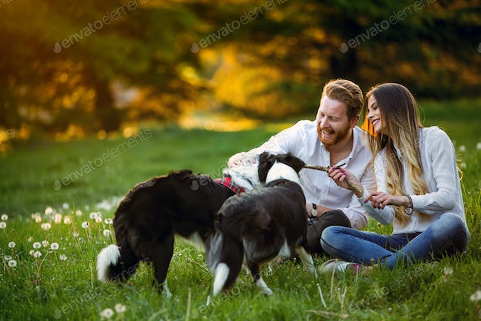Young couple in love walking and enjoy time in park with dogs