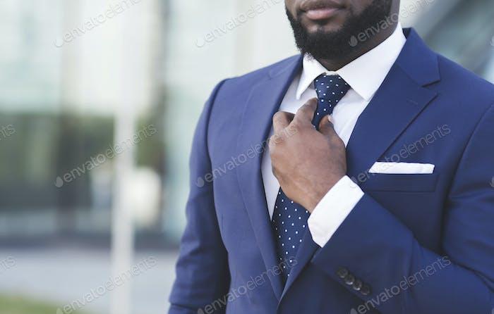 Unrecognizable Afro Man Adjusting Necktie Standing Outdoor In City