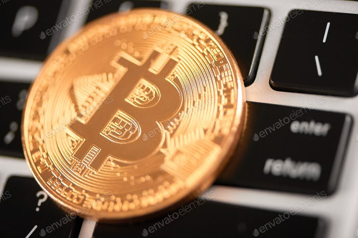 Closeup of golden bitcoin as main virtual currency placed on laptop keyboard