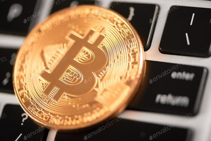 Nahaufnahme von goldenen Bitcoin als wichtigste virtuelle Währung auf Laptop-Tastatur platziert